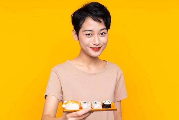 Młoda azjatycka kobieta z suszi z szczęśliwym wyrażeniem