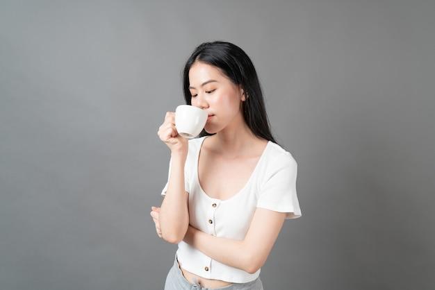 Młoda azjatycka kobieta z szczęśliwą twarzą i ręką trzymającą filiżankę kawy