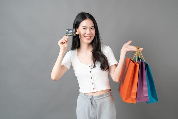 Młoda azjatycka kobieta za pomocą karty kredytowej i trzymając torbę na zakupy na szarej ścianie