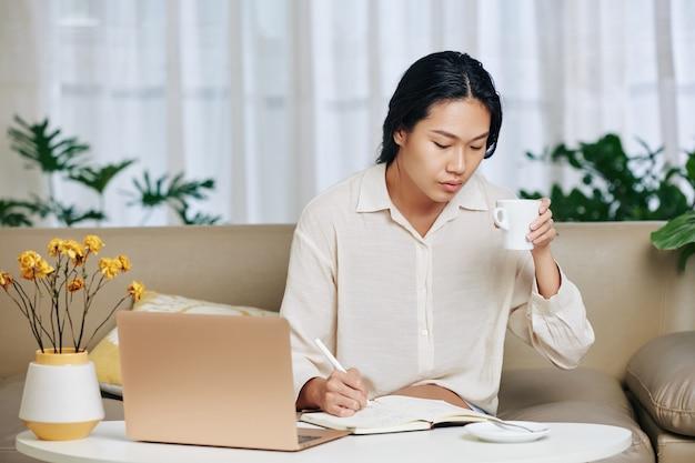 Młoda azjatycka kobieta zmęczona całodzienną pracą, piciem kawy i robieniem notatek w terminarzu