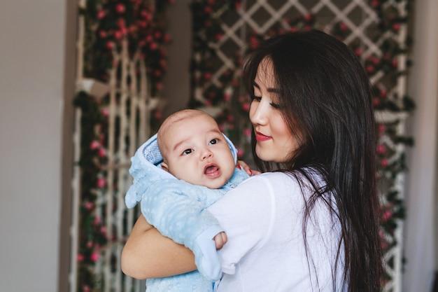 Młoda azjatycka matka i dziecko w pokoju.
