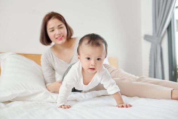 Młoda azjatycka matka odpoczywa na łóżku i patrząc na jej urocze pełzające dziecko