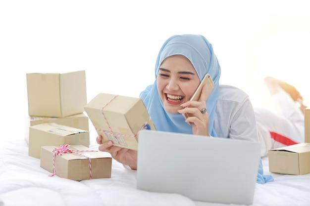 Młoda azjatycka muzułmanka leży na łóżku z komputerem i dostawą pudełek online i pracuje na telefonie komórkowym.