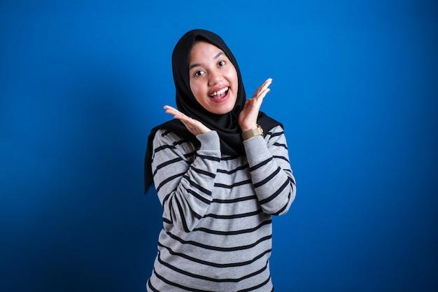 Młoda azjatycka muzułmanka ubrana w hidżab ze zdziwionym podekscytowanym krzykiem. wesoła dziewczyna ze śmiesznym radosnym wyrazem twarzy
