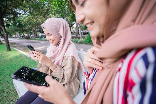 Młoda azjatycka muzułmanka w chuście na głowie spotyka się z przyjaciółmi i korzysta z telefonu w parku