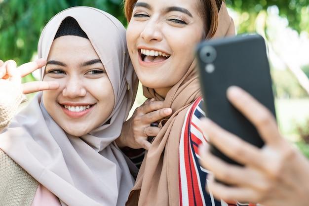 Młoda azjatycka muzułmanka w chuście na głowie spotyka się z przyjaciółmi i używa telefonu w parku do selfie lub połączeń wideo