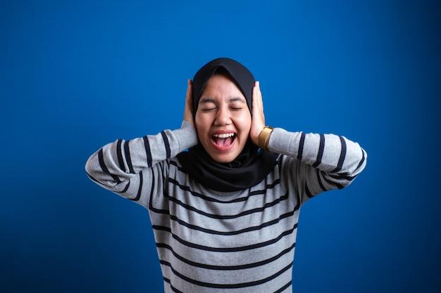 Młoda azjatycka muzułmanka w hidżab na białym tle na niebieskim tle. koncepcja życia religijnego ludzi. makieta miejsca na kopię. zakrywanie uszu palcami, zamykanie oczu, krzyczenie.