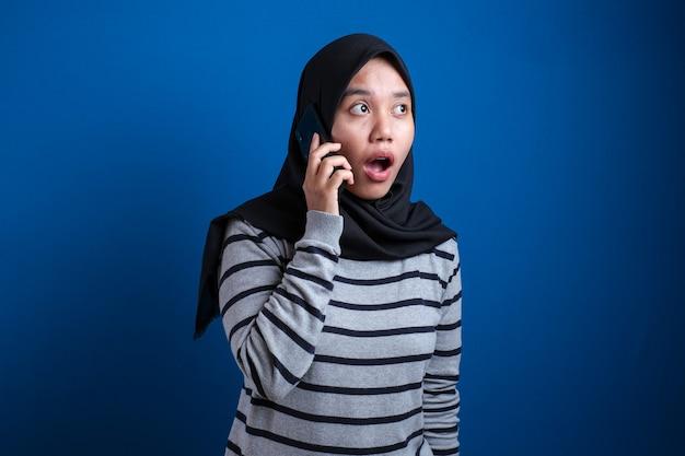 Młoda azjatycka muzułmanka w hidżabie pokazuje zszokowany wyraz twarzy podczas odbierania telefonu na niebieskim tle
