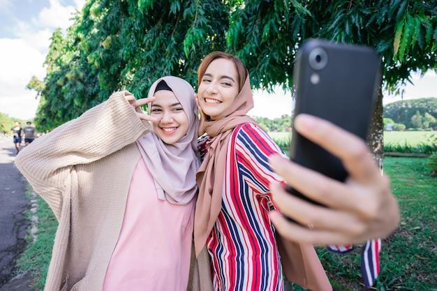 Młoda azjatycka muzułmanka w szaliku spotyka się z przyjaciółmi i używa telefonu w parku do selfie lub połączeń wideo