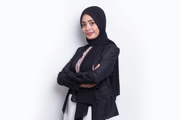 Młoda azjatycka muzułmańska biznesowa kobieta w uśmiechu na głowie z rękoma skrzyżowanymi na białym tle