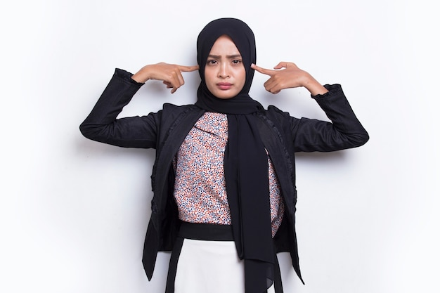 Młoda azjatycka muzułmańska biznesowa kobieta zakrywająca oba uszy rękami na białym tle