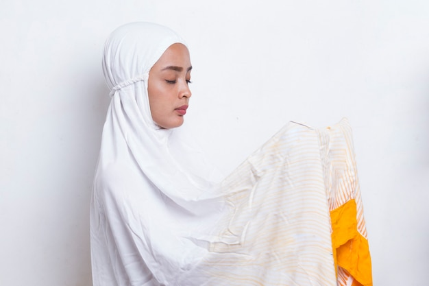 Młoda azjatycka muzułmańska kobieta modląca się na białym tle