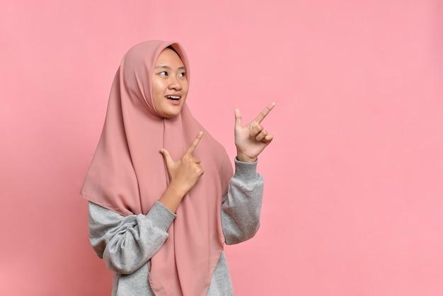 Młoda azjatycka muzułmańska kobieta uśmiecha się punktami na bok na przestrzeni kopii pokazuje reklamę noszącą muzułmańskie ubrania casual
