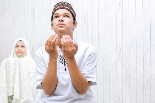 Młoda azjatycka muzułmańska para siedzi i modli się razem
