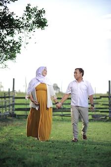 Młoda azjatycka muzułmańska para w ciąży chodzi i trzyma się za ręce na zielonej trawie