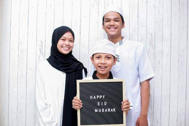 Młoda azjatycka muzułmańska rodzina w tradycyjnym stroju i chłopiec trzymający tablicę z literami mówi happy eid mubarak