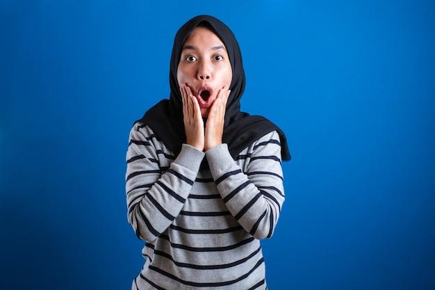 Młoda azjatycka muzułmańska studentka pokazuje zdziwioną lub zszokowaną minę z otwartymi ustami
