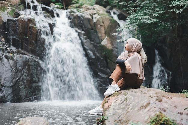 Młoda azjatycka muzułmańska turystka kobieta ubrana w brązowy hidżab siedzi na skale przed wodospadem.