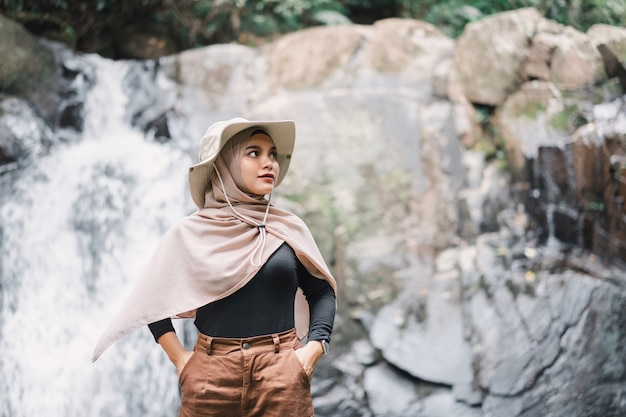 Młoda azjatycka muzułmańska turystka kobieta ubrana w brązowy hidżab stojący przed wodospadem.