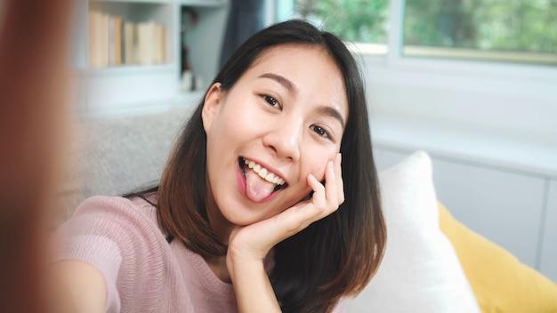 Młoda azjatycka nastolatek kobiety vlog w domu, kobieta używa smartphone robi vlog wideo ogólnospołeczni środki w żywym pokoju. styl życia kobieta relaksuje w ranku w domu pojęciu.