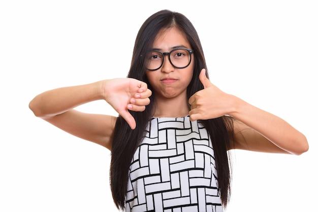 Młoda azjatycka nastolatka nerd daje kciuki w górę iw dół