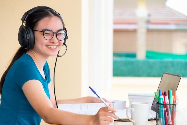 Młoda azjatycka nastolatka studentka z okularami słuchawkowymi patrzy podczas korzystania z laptopa, studiuje online ze szkolnej edukacji na odległość, ucząc się z klasy uniwersyteckiej w domu w tle