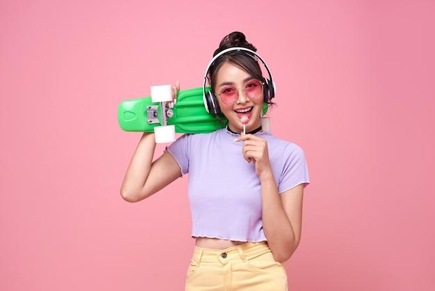Młoda azjatycka nastolatka trzyma deskorolkę z lizakiem na różowej ścianie.