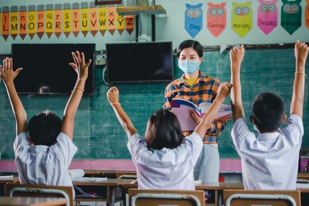 Młoda azjatycka nauczycielka z medyczną twarzą i uczniowie w wiejskiej tajskiej szkole uczą się