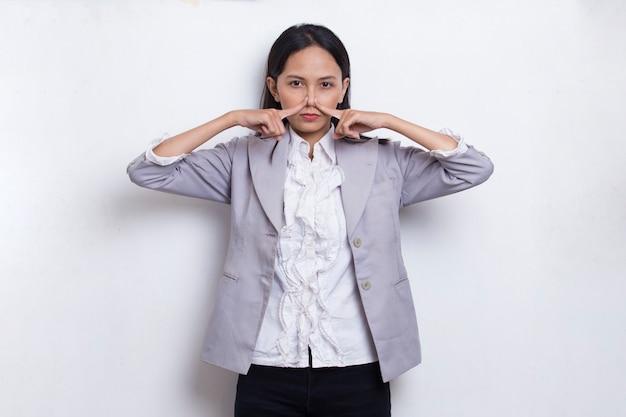 Młoda azjatycka piękna biznesowa kobieta trzyma nos z powodu złego zapachu czegoś