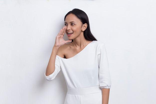 Młoda azjatycka piękna kobieta krzyczy i krzyczy ogłaszając na białym tle