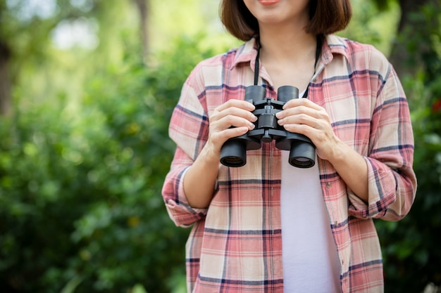 Młoda azjatycka piękna kobieta wygląda naturalnie i używa lornetki w publicznym parku z szczęśliwą twarzą stojącą i uśmiechniętą
