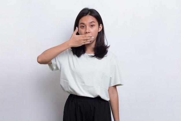 Młoda azjatycka piękna kobieta zszokowana zakrywając usta rękami za błąd na białym tle