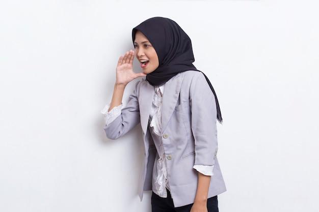 Młoda azjatycka piękna muzułmańska kobieta krzyczy i wrzeszczy, ogłaszając na białym tle