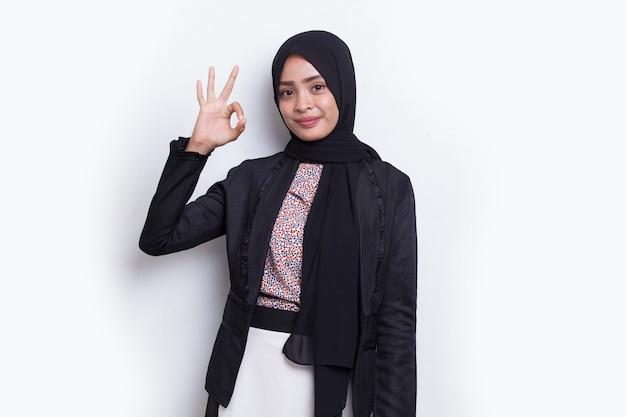 Młoda azjatycka piękna muzułmańska kobieta z ok znak gestem tumb up na białym tle