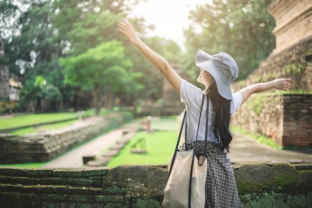 Młoda azjatycka podróżnik kobieta ono uśmiecha się podczas gdy podróżujący wokoło tajlandzkiej antycznej świątyni