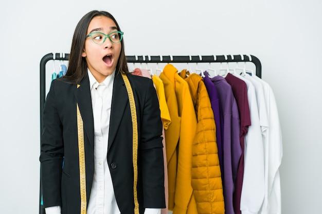 Młoda azjatycka projektantka kobieta na białej ścianie jest zszokowana czymś, co widziała.