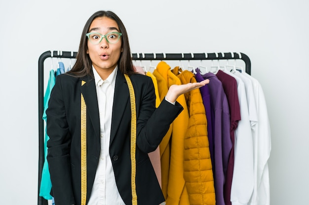 Młoda azjatycka projektantka kobieta na białej ścianie pod wrażeniem trzyma kopię na dłoni.
