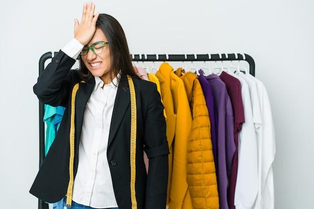Młoda azjatycka projektantka kobieta na białej ścianie zapominając o czymś, uderzając dłonią w czoło i zamykając oczy