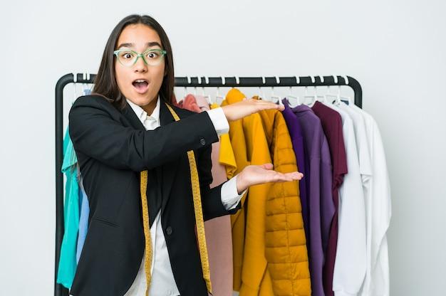 Młoda azjatycka projektantka kobieta na białej ścianie zszokowana i zdumiona trzyma kopię przestrzeni między rękami.