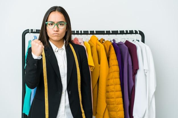 Młoda azjatycka projektantka kobieta na białym tle na białej ścianie pokazuje pięść, agresywny wyraz twarzy.