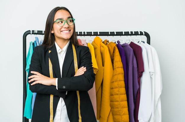 Młoda azjatycka projektantka kobieta na białym tle na białej ścianie, uśmiechając się pewnie ze skrzyżowanymi rękami.
