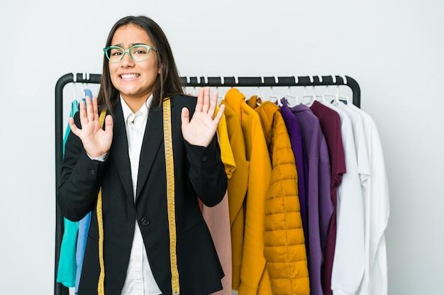Młoda azjatycka projektantka kobieta na białym tle odrzucająca kogoś pokazującego gest obrzydzenia.