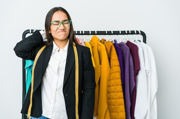 Młoda azjatycka projektantka na białej ścianie cierpi na ból szyi z powodu siedzącego trybu życia