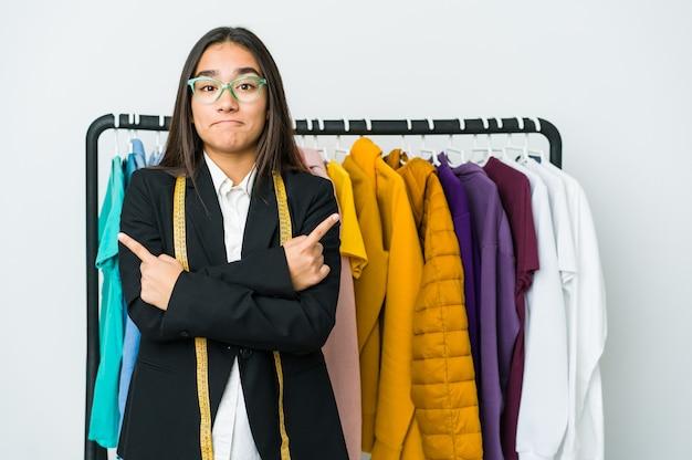 Młoda azjatycka projektantka na białej ścianie wskazuje na boki, próbuje wybrać jedną z dwóch opcji