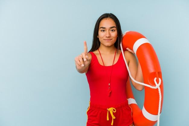 Młoda azjatycka ratownik kobieta na białym tle wyświetlono numer jeden z palcem