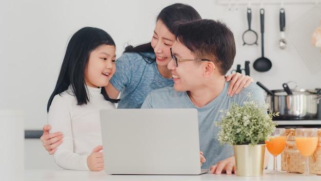 Młoda azjatycka rodzina cieszy się używać laptop w domu wpólnie. styl życia młody mąż, żona i córka szczęśliwie przytulają się i bawią po śniadaniu w nowoczesnej kuchni w domu rano.