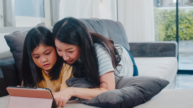 Młoda azjatycka rodzina i córka szczęśliwa używa pastylka w domu. japończyk matka relaksuje z małej dziewczynki dopatrywania filmu lying on the beach na kanapie w żywym pokoju przy domem. zabawna mama i cudowne dziecko dobrze się bawią.