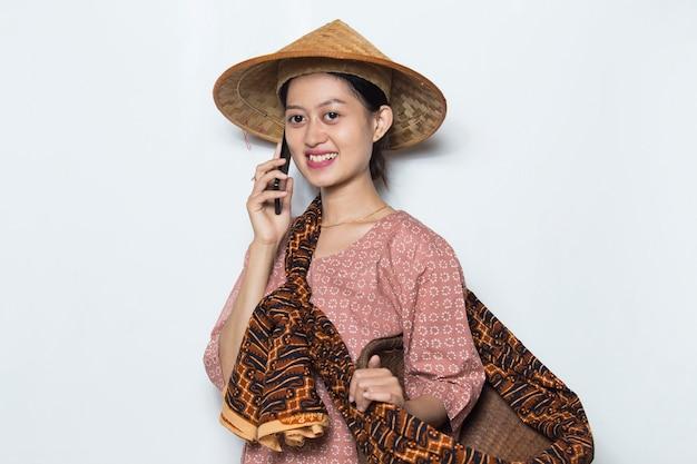 Młoda azjatycka rolniczka korzystająca z telefonu komórkowego na białym tle