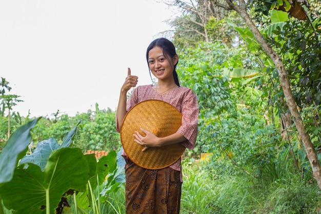 Młoda azjatycka rolniczka pokazująca kciuk w polu ryżowym
