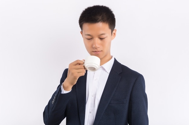 Młoda azjatycka samiec trzyma filiżankę kawy w jego ręce